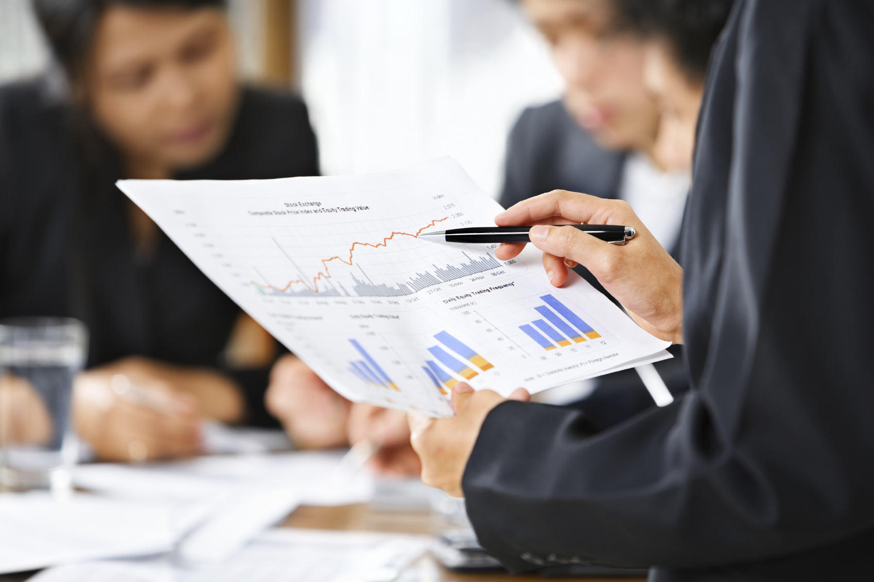 A business person, pointing to graphs and charts