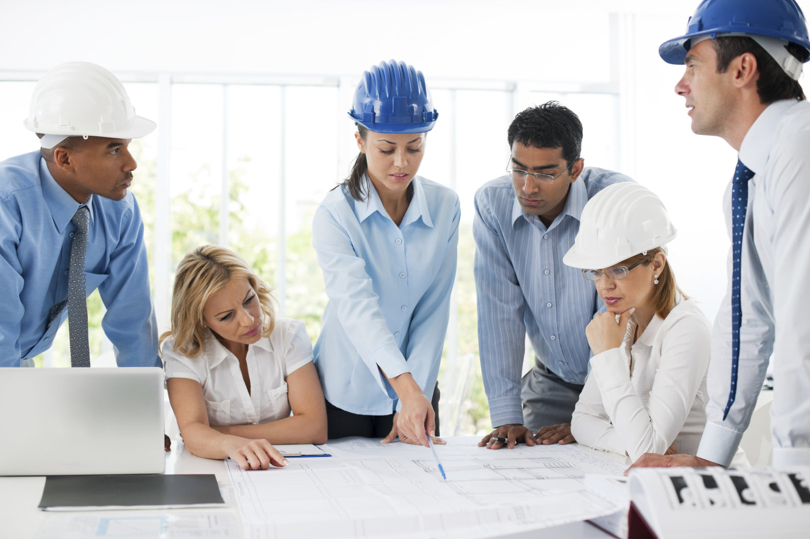 Six construction employees looking at blueprints
