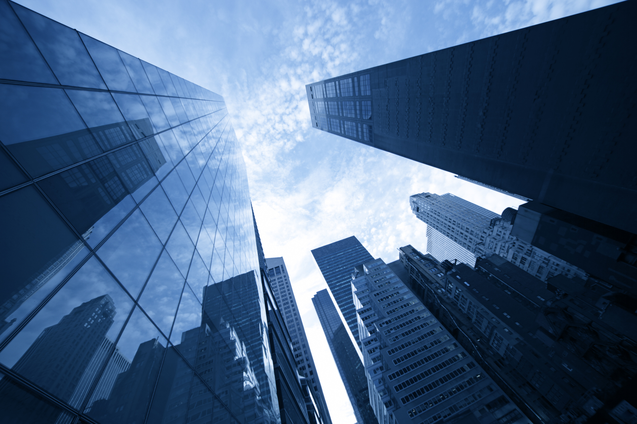 From the perspective of someone looking up at the sky, surrounded by tall buildings