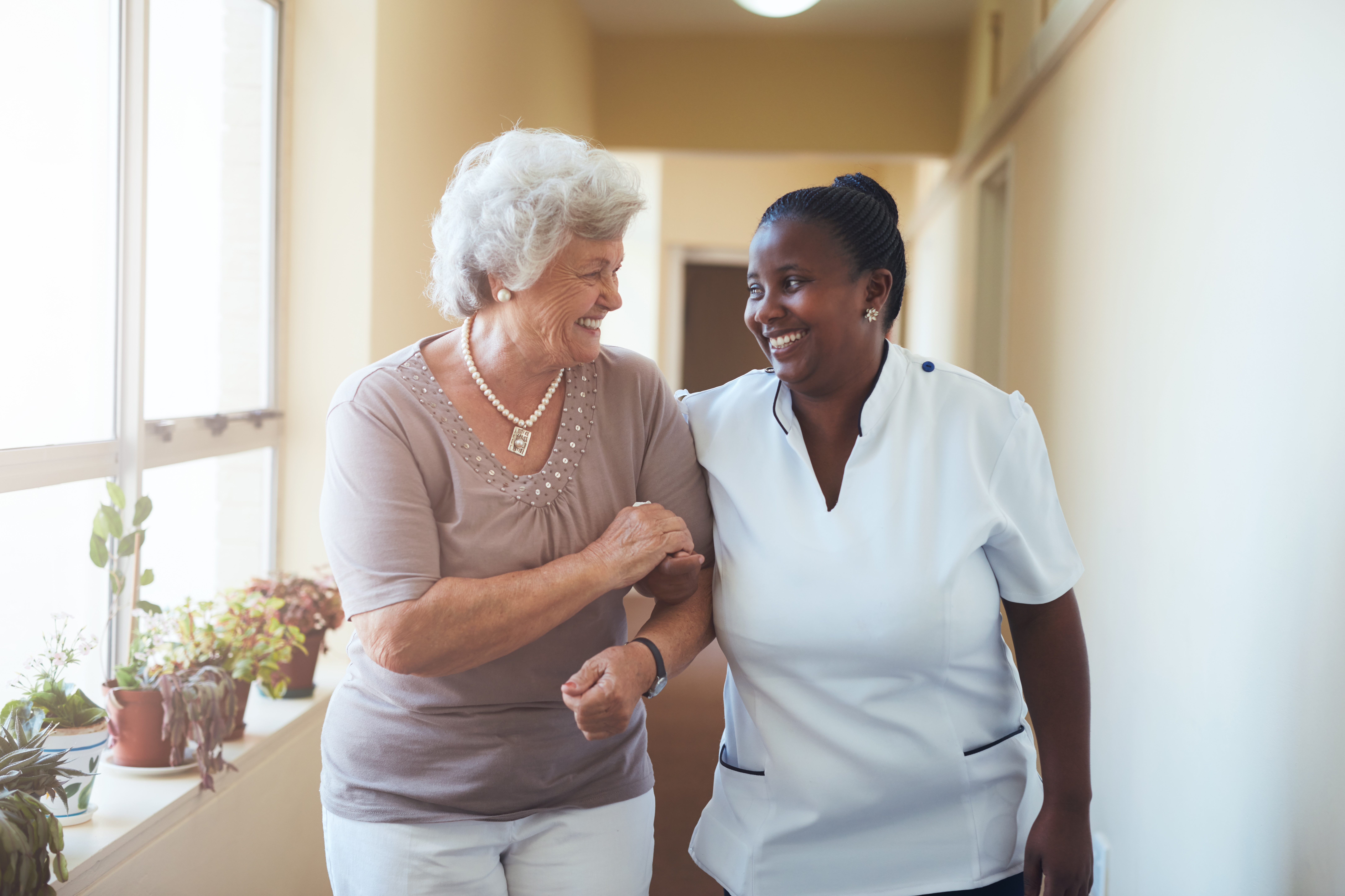 A healthcare worker escorting an older adult
